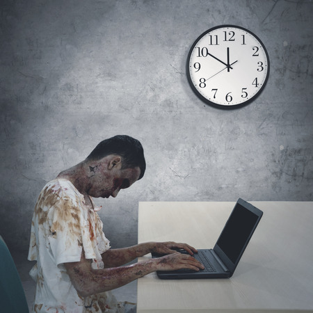 Image of zombie man looks tired during overworked in the office with a clock on the wall