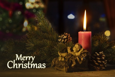 Foto de Merry Christmas text with a baby Jesus statue and burning candle on the table - Imagen libre de derechos