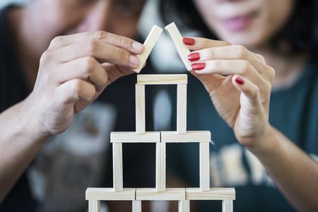 Foto de Dream house concept. Young couple playing wooden blocks and making a house shape - Imagen libre de derechos