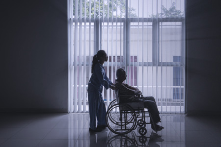 Photo pour Silhouette of female nurse pushing her elderly patient in a wheelchair while walking near the window - image libre de droit