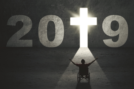 Silhouette of disabled man sitting in a wheelchair while looking numbers 2019 with bright cross symbolの写真素材