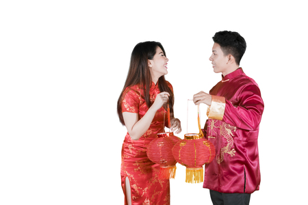 Foto de Picture of happy Asian couple carrying red lantern at Chinese new year in the studio, isolated on white background - Imagen libre de derechos