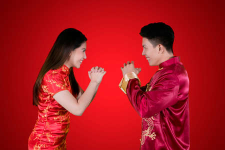 Photo pour Image of young Chinese couple wearing cheongsam dress while congratulating each other. Shot in red background - image libre de droit