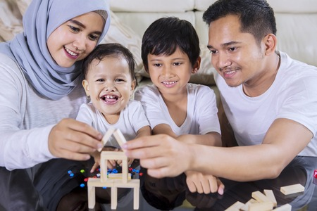 Foto de Image of happy family playing with wood blocks to build a dream house while sitting in the living room - Imagen libre de derechos