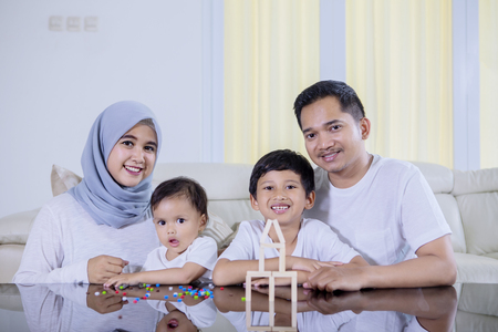 Photo pour Picture of young family sitting in the living room while playing with wood blocks to build a dream house - image libre de droit