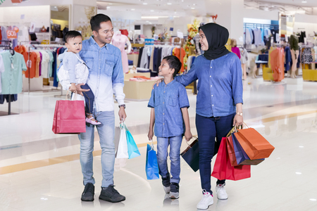 Foto de Picture of a happy Muslim family holding shopping bags while walking together in the mall - Imagen libre de derechos
