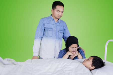 Picture of young parent looks sad while accompanying their sick son in the studio with green screen
