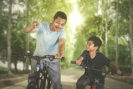 Image of young man riding a bicycle with his son while pointing at something in the roadの写真素材