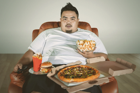 Photo pour Picture of an obese man watching TV on the sofa while eating junk foods at home  - image libre de droit