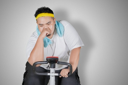 Foto de Image of tired obese man doing workout with exercise bike in the studio - Imagen libre de derechos