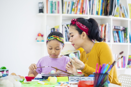 Photo for Young woman and her daughter coloring eggs for Easter in the library - Royalty Free Image