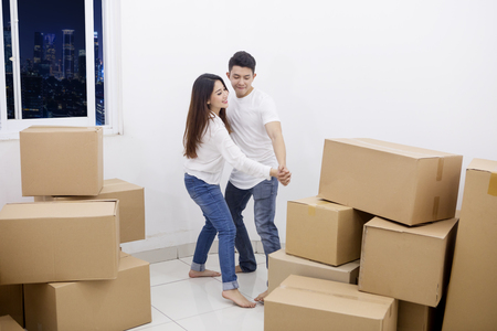 Photo for Image of a young couple dancing after moving into their new apartment with piles of cardboard boxes - Royalty Free Image