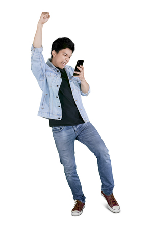 Foto de Full length of a young happy man holding a mobile phone while celebrating his success in the studio - Imagen libre de derechos