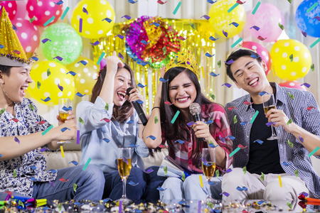 Photo pour Two young couples singing together while drinking champagne at a birthday party - image libre de droit