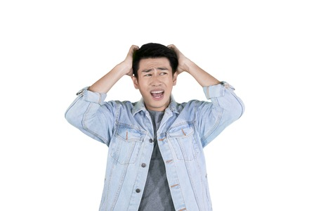 Foto de Young Asian man having headache while holding his head and standing in the studio, isolated on white background - Imagen libre de derechos