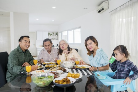 Foto de Picture of extended family looks happy while eating meals together at the dining table. Shot at home - Imagen libre de derechos