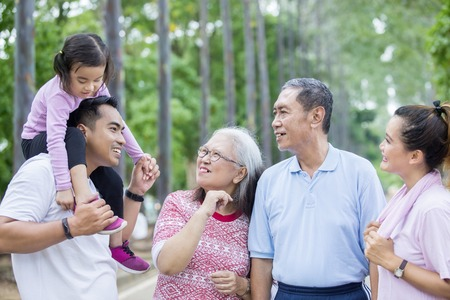 Photo pour Picture of extended family talking each other after doing exercise together in the park - image libre de droit