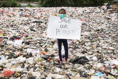 Photo pour JAKARTA - Indonesia. May 27, 2019: Little girl showing a paper with text of Save Our Planet in while standing in the landfill - image libre de droit