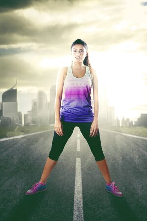 Photo pour Young woman wearing sportswear and standing on the street and reading for exercising - image libre de droit