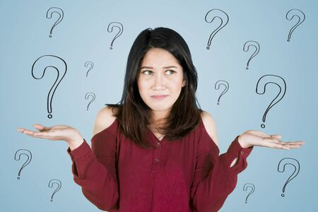 Photo pour Picture of young Asian woman looks confused while standing with question marks - image libre de droit