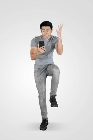 Foto de Full length of young Asian man looks shocked while using a mobile phone in the studio - Imagen libre de derechos