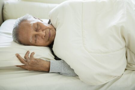 Foto de Picture of elderly man wrapped with a blanket while sleeping on a bed. Shot in the bedroom - Imagen libre de derechos
