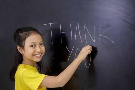 Photo pour Teacher appreciation Concept. Female elementary school student writing thank you text on blackboard in the classroom - image libre de droit