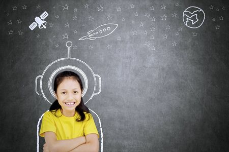 Photo for Picture of confident schoolgirl smiling at the camera while imagining being an astronaut - Royalty Free Image