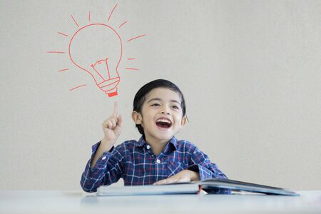 Photo for Picture of little boy reading book while thinking an idea and sitting under a drawn light bulb background - Royalty Free Image