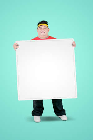 Photo for Portrait of an obese man wearing sportswear while holding a blank whiteboard in the studio - Royalty Free Image