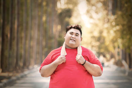 Photo pour Portrait of Asian fat man wearing sportswear while standing on the road at autumn time - image libre de droit