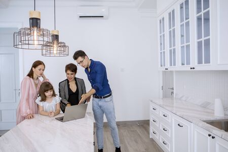 Photo pour Picture of Caucasian family consulting a new house with their real estate agent - image libre de droit