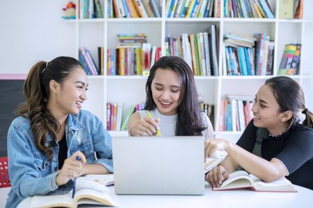Foto de Group of female teenagers looks happy while studying together in the library with bookcase background - Imagen libre de derechos