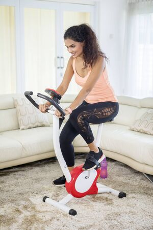Photo pour Portrait of young Indian woman doing a workout with an exercise bike in the living room. Shot at home - image libre de droit