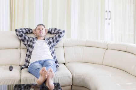 Foto de Portrait of a Caucasian man resting on the sofa while watching TV in the living room. Shot at home - Imagen libre de derechos