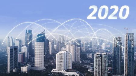 Foto de Aerial view of skyscrapers with numbers 2020 and network connection at morning time in Jakarta city - Imagen libre de derechos