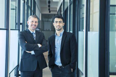 Photo pour Confident multiethnic businessmen standing in an office corridor - image libre de droit