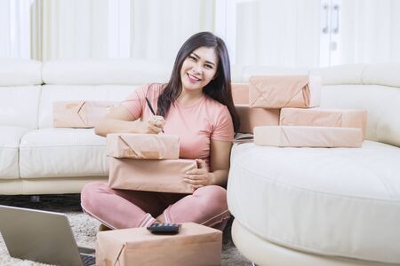Photo pour Beautiful Asian woman smiling to camera while writing and naming one of the boxes in her living room - image libre de droit