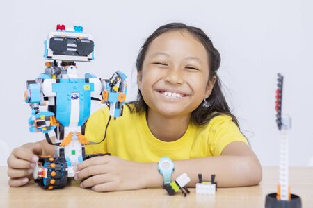 Photo pour Portrait of an Asian kid presenting her finished robot project with pride - image libre de droit