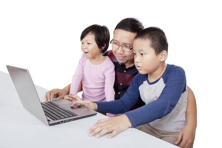Foto de Portrait of handsome Asian man teaching his children how to use a computer wisely, isolated in white background - Imagen libre de derechos