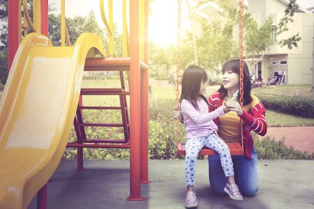 Beautiful Asian woman accompanying her daughter swinging at the park