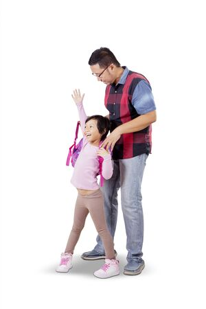 Handsome Asian man wearing backpack to her daughter happily and joyfully while accompanying her back to school, isolated in white background
