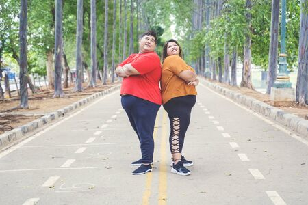 Fat Asian couple wearing sportswear while posing & looking each other by crossing their arms proudly on the road at the park