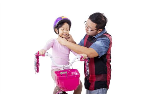 Photo pour Portrait of handsome Asian man putting a bike helmet for his daughter with care while kneeling, isolated in white background - image libre de droit