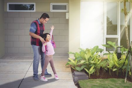 Handsome Asian man wearing backpack for her daughter, while accompanying her back to school at their house yard