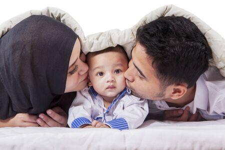 Photo pour Portrait of happy young parents kissing their baby under blanket on the bed - image libre de droit