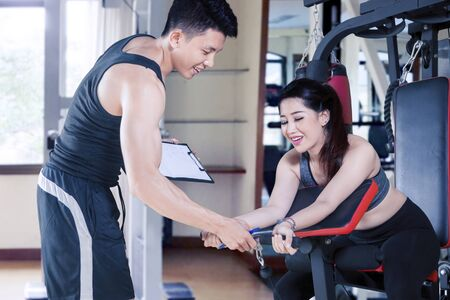 Photo pour Young personal trainer helping young woman exercising on gym equipment at fitness center - image libre de droit