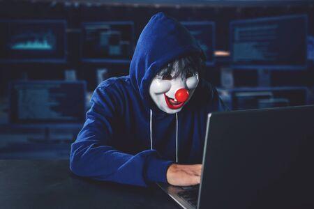 Foto de Hacker wearing clown mask hacking on a laptop computer with computer monitors background - Imagen libre de derechos