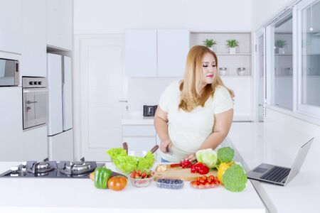 Photo for Portrait of pretty obese woman making vegetable salad while looking at a laptop computer in the kitchen at home - Royalty Free Image