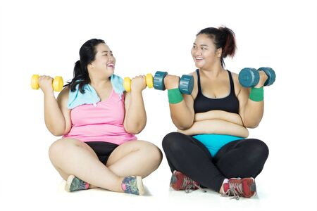 Foto für Two overweight women exercising with dumbbells while sitting in the studio, isolated on white background - Lizenzfreies Bild